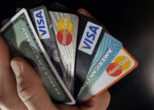 In this March 5, 2012, file photo, consumer credit cards are posed in North Andover, Mass. The three largest credit reporting agencies will change the way they handle records in a major revamp long sought by consumer advocates. The changes were announced Monday, March 9, 2015, after talks between Equifax, Experian, TransUnion and New York Attorney General Eric Schneiderman. (AP Photo/Elise Amendola, File)