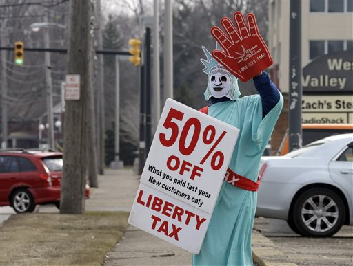 In this March 21, 2015 photo, Brittney Freison, dressed as Lady Liberty, waves to motorists near the Liberty Tax Service office in Berea, Ohio. Wary of rising fees, federal regulators are eyeing ways they can assert tighter oversight upon paid tax preparers who cater to an expanding market of cash-strapped families anxious for their tax refunds. (AP Photo/Mark Duncan)