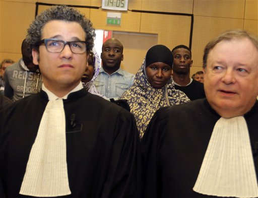 Zyed Benna's father Amor Benna, background left,  Aissatou Traore, center right, sister of Bouna Traore, plaintiffs' lawyers Emmanuel Tordjman, foreground and Jean-Pierre Mignard, right, stand at the Rennes courtroom, western France, Monday, March 16, 2015. Two police officers go on trial over the deaths of  minority teenagers Zyed Benna and Bouna Troare  in a troubled Paris suburb, in 2005, deaths that prompted weeks of national riots and exposed deep discrimination and social tensions that France has failed to mend a decade later. (AP Photo/David Vincent)