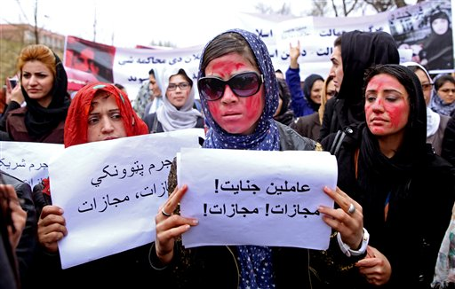 """Afghan women, demand justice for a woman who was beaten to death by a mob after being falsely accused of burning a Quran last week, during a protest in downtown Kabul, Afghanistan, Tuesday, March 24, 2015. Men and women of all ages carried banners bearing the bloodied face of Farkhunda, a 27-year-old religious scholar killed last week by a mob. Farkhunda, who went by one name like many Afghans, was beaten, run over with a car and burned before her body was thrown into the Kabul River. The poster at center with Persian writing reads, """"Farkhunda's murderers, execution."""" (AP Photo/Massoud Hossaini)"""