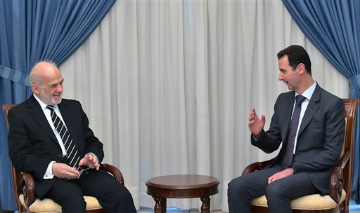 """In this photo released by the Syrian official news agency SANA, Syrian president Bashar Assad, right, speaks with Iraqi Foreign Minister Ibrahim al-Jaafari, left, in Damascus, Syria, Tuesday, March. 24, 2015. Al-Jaafari said they discussed """"Syrian and Iraqi issues, and the common dangers that threaten our security."""" (AP Photo/SANA)"""