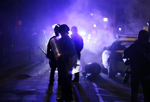 "In this Nov. 25, 2014 file photo, police officers watch protesters as smoke fills the streets in Ferguson, Mo. after a grand jury's decision in the fatal shooting of Michael Brown. Six months after 18-year-old Michael Brown died in the street in Ferguson, Missouri, the Justice Department is close to announcing its findings in the racially charged police shooting that launched ""hands up, don't shoot"" protests across the nation. (AP Photo/Charlie Riedel, File)"