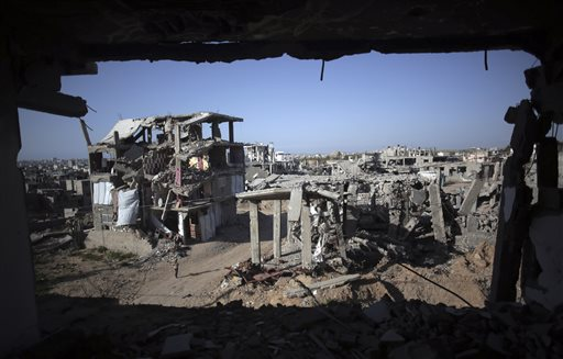 A Palestinian girl walks next to destroyed houses, in the Shijaiyah neighborhood of Gaza City, Monday, March 30, 2015. Despondent over the slow pace of post-war reconstruction, displaced Gazans have begun to return to their damaged homes, patching up the structures with blankets and plastic sheets and living in the unstable and unsafe structures while they wait for promised aid to arrive. (AP Photo/Khalil Hamra)