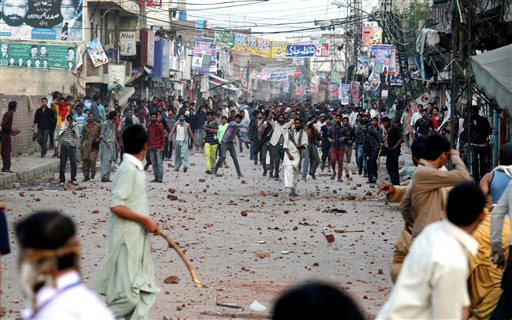 Pakistani protesters throw rocks during clashes with police to condemn Sunday's suicide bombings that struck two churches, in Lahore, Pakistan, Monday, March 16, 2015. Pakistani police fired tear gas on Monday after Christian protesters clashed with police in the eastern city of Lahore, a day after Taliban bombers killed more than a dozen people in suicide attacks on two churches in the city. (AP Photo/K.M. Chaudary)