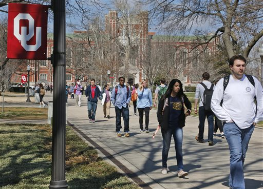 People walk on the Oval at the University of Oklahoma in Norman, Okla., Tuesday, March 10, 2015. Two students have been expelled from the university following an incident in which members of a fraternity were caught on video chanting a racial slur. (AP Photo/Sue Ogrocki)