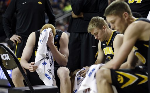 In this March 22, 2015, file photo, Iowa's Aaron White, left, and teammates rest during a timeout against Gonzaga in the second half of an NCAA tournament college basketball game in the Round of 32 in Seattle. In the NCAA tournament, more frequent stoppages in play-- leave coaches and players with time on their hands. (AP Photo/Elaine Thompson, File)