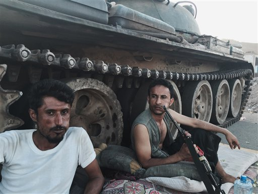 In this March 21, 2015, photo, Members of a militia group loyal to Yemen's President Abed Rabbo Mansour Hadi, known as the Popular Committees, chew qat as they sit next to their tank, guarding a major intersection in Aden, Yemen. Once hailed by President Barack Obama as a model for fighting extremism, the U.S. counterterrorism strategy in Yemen has all but collapsed as the country descends into chaos, according to U.S. and Yemeni officials. (AP Photo/Hamza Hendawi, File)