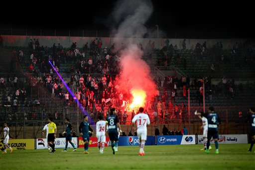 In this Sunday, Feb. 8, 2015 file photo, Ultras White Knights soccer fans light flares during a match between Egyptian Premier League clubs Zamalek and ENPPI at the Air Defense Stadium in a suburb east of Cairo, Egypt. At least 22 soccer fans were crushed to death outside an air defense stadium in Cairo after police fired tear gas to break up the crowd waiting in a fenced, narrow corridor to watch. Police accused the fans of attacking the force, and rioting to enter the stadium. On Tuesday, March, 17, 2015 the chief prosecutor general also referred 16 fans to trial, accusing them of belonging to the Muslim Brotherhood. (AP Photo/Ahmed Abd El-Gwad, El Shorouk Newspaper, File)