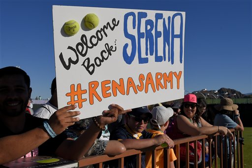 Tennis fans hold a sign for Serena Williams as they wait for her to pass by before she faces Monica Niculescu, of Romania, in their match at the BNP Paribas Open tennis tournament, Friday, March 13, 2015, in Indian Wells, Calif. (AP Photo/Mark J. Terrill)