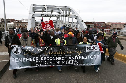 """People cross Edmund Pettus Bridge marching towards Montgomery, Monday, March 9, 2015, in Selma, Ala.to mark the 50th anniversary of """"Bloody Sunday,"""" a civil rights march in which protesters were beaten, trampled and tear-gassed by police at the Edmund Pettus Bridge in Selma, Ala. (AP Photo/Butch Dill)"""