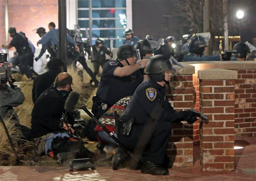 Police take cover after two officers were shot while standing guard in front of the Ferguson Police Station on Thursday, March 12, 2015.  (AP Photo/St. Louis Post-Dispatch, Laurie Skrivan)