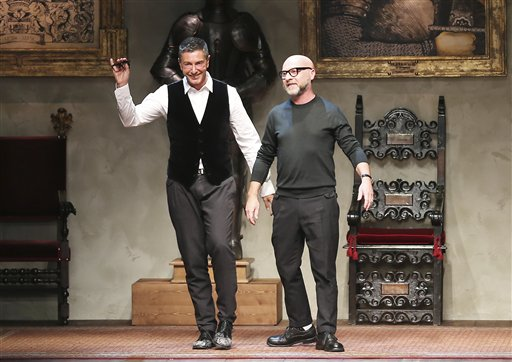 In this Jan. 11, 2014 file photo Italian fashion designers Domenico Dolce, right, and Stefano Gabbana acknowledge the applause of the audience after a men's Autumn-Winter 2014 collection, part of the Milan Fashion Week, unveiled in Milan, Italy. The designers have defended Sunday, March 15, 2015 their comments in support of traditional families, saying they were not intended to judge the choices made by others. The comments in an interview this week unleashed a call to boycott the designers' Dolce&Gabbana label, joined by Elton John whose children were conceived by in vitro fertilization. (AP Photo/Antonio Calanni, File)