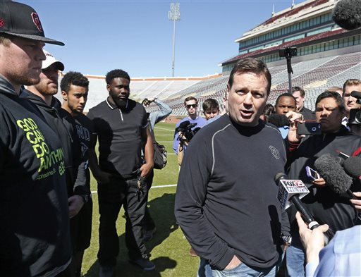 Oklahoma head coach Bob Stoops, center, answers a question for reposters following a demonstration by the Oklahoma football team against racism in Norman, Okla., Thursday, March 12, 2015. Looking on, from left, are players Ty Darlington, Trevor Knight, Zack Sanchez and Charles Tapper. (AP Photo/Sue Ogrocki)