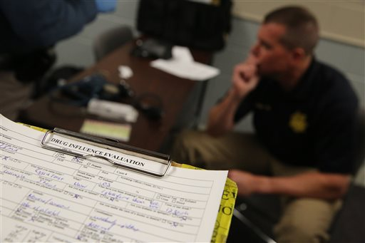 In this March 6, 2014 file photo, an instructor for a Drug Recognition Expert class, sits near a completed roadside Drug Influence Evaluation sheet on a clipboard, at the Colorado State Patrol Training Academy, in Golden, Colo.  Legalizing marijuana reduces drug arrests but doesn't solve one of the central goals of drug-policy reformers, ending racial disparities in marijuana enforcement. That's according to a new review of Colorado's criminal justice system before and after pot was made legal.  (AP Photo/Brennan Linsley, file)