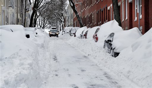 A car makes its way down a street filled with snowed-in vehicles in Boston's Charlestown section, Wednesday, Jan. 28, 2015 one day after a blizzard dumped about two feet of snow in the city. (AP Photo/Elise Amendola)