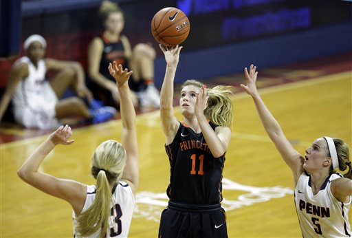 Princeton guard Blake Dietrick (11) takes a shot as she splits Pennsylvania defenders Sydney Stipanovich (13) and Kathleen Roche (5) during the first half of an NCAA college basketball game Tuesday, March 10, 2015, in Philadelphia, Pa. (AP Photo/Mel Evans)