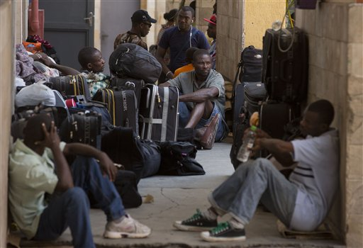 In this Jan. 13, 2015 photo, Haitian migrants wait to find a place to sleep and employment outside Our Lady of Peace Catholic Church which helps recently arrived migrants in Sao Paulo, Brazil. Trying to survive on sporadic and meager incomes, most Haitin migrants crowd into shared rooms amid the poorest slums ringing cities such as Sao Paulo. (AP Photo/Andre Penner)