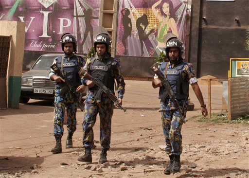 The nightclub, rear, that was attacked by gunmen as armed forces provide security in Bamako, Mali, Saturday, March 7, 2015. A masked gunman sprayed bullets around a nightclub popular with foreigners in Mali's capital early Saturday, killing at least five people including a French person and a Belgian national, officials and witnesses said. (AP Photo/Harouna Traore)