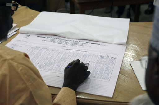 A Nigerian election official reads local results in Kaduna, Nigeria Monday, March 30, 2015, as the collation of votes for last Saturday's elections starts in Abuja. Nigerians are waiting in hope and fear for results of the tightest and most bitterly contested presidential election in the nation's turbulent history. (AP Photo/Jerome Delay)