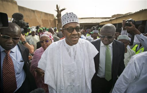 Opposition candidate Gen. Muhammadu Buhari, center, arrives to validate his voting card using a fingerprint reader, prior to casting his vote later in the day, in his home town of Daura, Nigeria Saturday, March 28, 2015. Nigerians went to the polls Saturday in presidential elections which analysts say will be the most tightly contested in the history of Africa's richest nation and its largest democracy. (AP Photo/Ben Curtis)