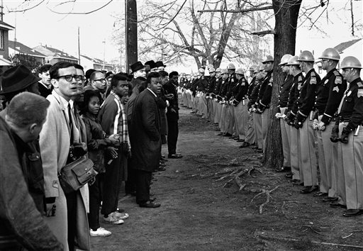 In this March 13, 1965 file photo, a line of police officers hold back demonstrators who attempted to march to the courthouse in Selma, Ala. Police kept the demonstrators hemmed up in a square block area where they attempted several times to break through. (AP Photo/File)