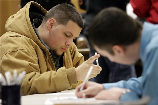 In this Jan. 29, 2015 file photo, Tyler Kelly, 19,  left, fills out applications for parking enforcement and environmental compliance jobs during a public safety job fair at City Hall in Saginaw, Mich. The  Labor Department releases job openings and labor turnover survey for January on Tuesday, March 10, 2015.  (AP Photo/The Saginaw News, David C. Bristow)