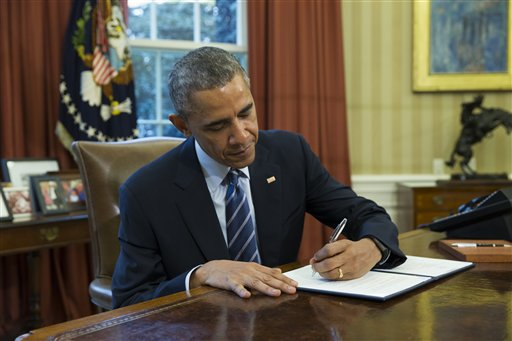 President Barack Obama signs a presidential memorandum aiming to clamp down on the private companies that service federal student debt, Tuesday, March 10, 2015, in the Oval Office of the White House in Washington. (AP Photo/ Evan Vucci)