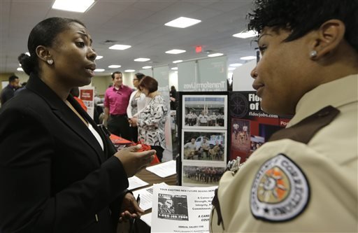 In this photo taken Friday, Feb. 6, 2015, U.S. Army Veteran Patricia Jeanty, of Tamarac, left, talks to job possibilities with Sergeant Latina Smith, right,  of the Florida Department of Corrections at the annual Veterans Career and Resource Fair in Miami. The U.S. Labor Department reports on the number of people who applied for unemployment benefits during the week ending March 14 on Thursday, March 19, 2015. (AP Photo/Alan Diaz)