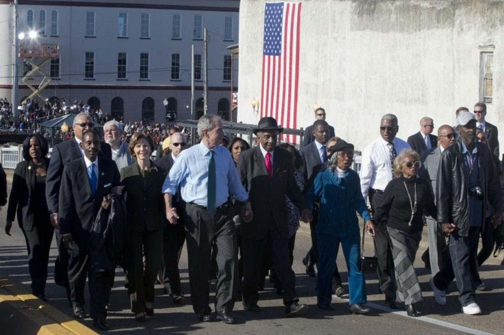 """Laura Bush, second from left, and former President George W. Bush, as well as members of Congress and civil rights leaders make a symbolic walk across the Edmund Pettus Bridge in Selma, Ala., for the 50th anniversary of """"Bloody Sunday,"""" a landmark event of the civil rights movement, Saturday, March 7, 2015. (AP Photo/Jacquelyn Martin)"""