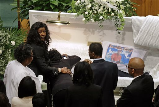 Gloria Darden, mother of Freddie Gray, is comforted as she embraces his body before his funeral, Monday, April 27, 2015, at New Shiloh Baptist Church in Baltimore. Gray died from spinal injuries about a week after he was arrested and transported in a Baltimore Police Department van. (AP Photo/Patrick Semansky)
