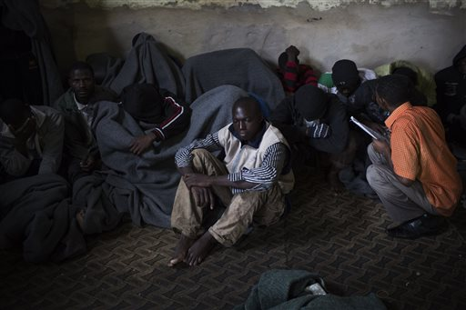In this file photo taken Friday, Nov. 29, 2013, African migrants cover themselves with blankets, after being captured by the Libyan Coast Guard while on a boat heading to Italy, in a detention center for illegal migrants in Abu Salim district on the outskirts of Tripoli, Libya. Libya's chaos has turned it into a large and lucrative funnel attracting migrants desperate to make the dangerous sea voyage to Europe. With no central authority to stop it, business is booming, creating a vicious circle that only translates into more tragedies in the Mediterranean. (AP Photo/Manu Brabo, File)