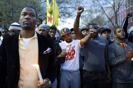 Protesters stand outside the Baltimore Police Department's Western District police station at the end of a march for Freddie Gray, Tuesday, April 21, 2015, in Baltimore. Gray died from spinal injuries about a week after he was arrested and transported in a police van. (AP Photo/Patrick Semansky)