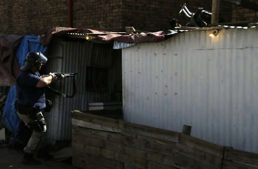 An armed police officer approaching a hostel in Astonville near Johannesburg, Thursday, April 16, 2015, during an anti-immigrant protest. South African President Jacob Zuma on Thursday urged South Africans to stop attacking immigrants from the rest of Africa and South Asia, after days of violence have left at least five people dead, escalating fears of violence and sending foreigners to seek refuge in various camps and police stations. (AP Photo/Themba Hadebe)