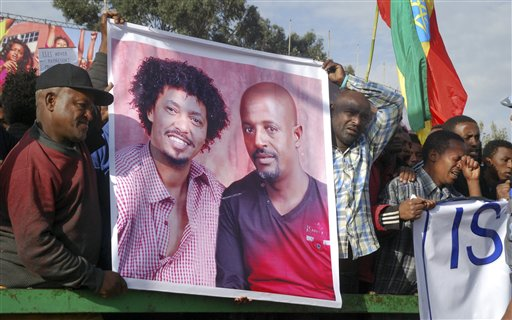 "Protesters hold a banner showing victims Eyasu Yikunoamlak, left, and Balcha Belete, right, at a government-supported gathering to protest the recent killing of many Ethiopian Christians in Libya by the Islamic State extremist group, at Meskel Square in Addis Ababa, Ethiopia Wednesday, April 22, 2015. Some stone-throwing protesters clashed with police and directed their anger at Ethiopia's government, seen by some as not doing enough to raise the living standards of the most vulnerable people, while others raised slogans including one that said ""We want revenge for our sons' blood,"" referring to Ethiopians seen being beheaded or shot in a video released by the Islamic extremist group Islamic State. (AP Photo)"
