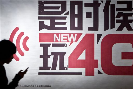 In this March 9, 2013 photo, a woman uses her phone as she walks by an advertisement for a 4G telecommunications network in Hangzhou, in eastern China's Zhejiang province. On Wednesday, April 15, 2015, the World Bank said the number of people opening their first bank accounts - either on mobile phones or at bank branches - jumped by 700 million between 2011 and 2014. (CHINATOPIX via AP)