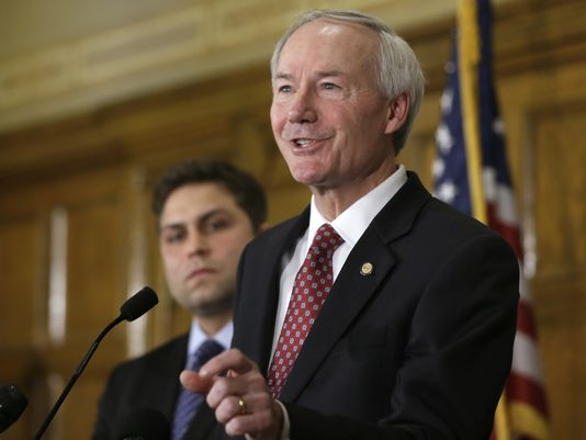 Arkansas Gov. Asa Hutchinson, right, answers reporters' questions as Sen. Jonathan Dismang, R-Beebe, listens at the state Capitol in Little Rock on Wednesday. (Danny Johnston/AP Photo)