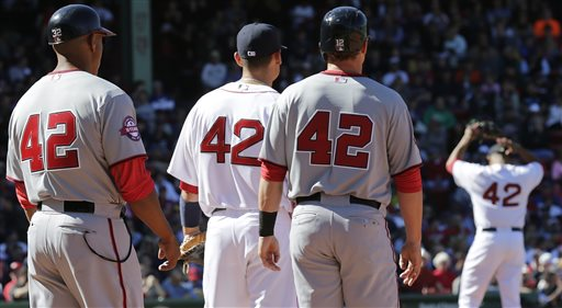 With all players and coaches wearing #42 in remembrance of Jackie Robinson, Boston Red Sox relief pitcher Anthony Varvaro, right, sets to pitch during a baseball game at Fenway Park in Boston, Wednesday, April 15, 2015. Robinson broke Major League Baseball's color barrier on April 15, 1947, taking the field as the first African-American player for the Brooklyn Dodgers. From left are Nationals first base coach Tony Tarasco, Red Sox first baseman Mike Napoli, Nationals base runner Tyler Moore and Varvaro. (AP Photo/Charles Krupa)