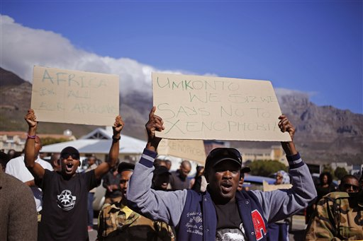 A man hold a placard, left, reading 'Africa is all for Africans'  prior to a march against immigrant attacks in South Africa, in Cape Town, South Africa, Wednesday, April 22, 2015. Police and soldiers officers raided a hostel considered a hotspot for anti-immigrant attacks in downtown Johannesburg as South Africa continued a crackdown in xenophobic violence. (AP Photo/Schalk van Zuydam)
