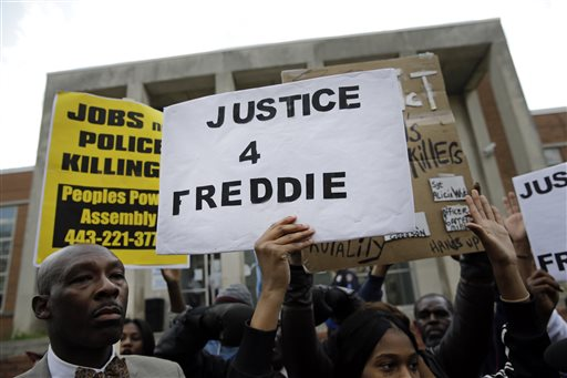 Protestors stand outside of the Baltimore Police Department's Western District police station during a march and vigil for Freddie Gray, Tuesday, April 21, 2015, in Baltimore. Gray died from spinal injuries a week after he was arrested and transported in a police van. (AP Photo/Patrick Semansky)