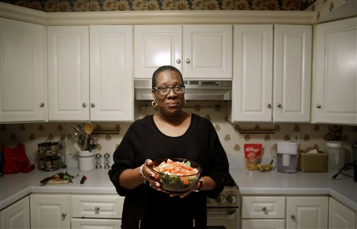 In this April 3, 2015 photo, Michele Rouse holds a salad that she made in her kitchen in Edgewood, Md. Rouse says she has lost 7 pounds since she started on Weight Watchers a month ago and has already seen a drop in her elevated blood pressure. Weight Watchers and Jenny Craig scored the best marks for effectiveness in a review of research on commercial diet programs, but many other plans just haven't been studied enough to evaluate long-term results. (AP Photo/Patrick Semansky)