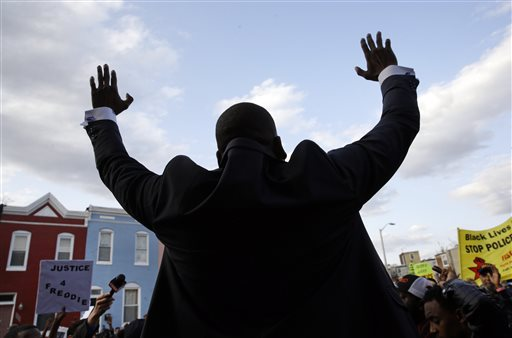 Rev. Jamal Bryant raises his hands as he speaks during a vigil and march for Freddie Gray, Tuesday, April 21, 2015, in Baltimore. Gray died from spinal injuries a week after he was arrested and transported in a police van. (AP Photo/Patrick Semansky)
