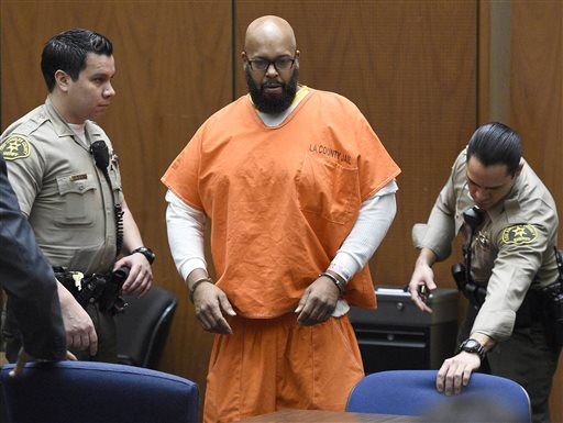 """In this March 9, 2015 file photo, Marion """"Suge"""" Knight, center, arrives in court for a hearing about evidence in his murder case, in Los Angeles. Knight will stand trial on murder and attempted-murder charges after the former rap music mogul struck two men with his pickup truck in January, killing one and seriously injuring the other. Superior Court Judge Ronald Coen made the ruling Thursday after concluding a hearing that focused heavily on testimony from Cle """"Bone"""" Sloan, who was hit outside a Compton burger stand. The judge also reduced bail from $25 million to $10 million. (Kevork Djansezian/Pool Photo via AP, File)"""