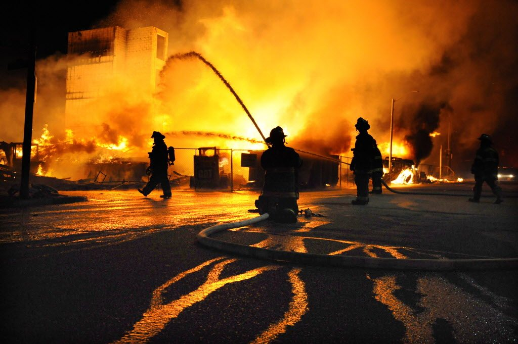 Baltimore firefighters battle a three-alarm fire Monday, April 27, 2015,  at a senior living facility under construction at Federal and Chester Streets in East Baltimore. It was unclear whether is was related to the ongoing riots but was one of several fires in the area. (Jerry Jackson/The Baltimore Sun via AP)
