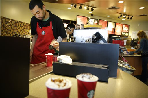 In this Nov. 24, 2014, file photo, barista Jay Rapp prepares a Chestnut Praline Latte at a Starbucks store in Seattle. Starbucks on Monday, April 6, 2015, said its workers can now have four years of tuition covered for an online college degree from Arizona State University instead of just two, marking the latest sign that companies are rethinking their treatment of low-wage workers. (AP Photo/Ted S. Warren, File)