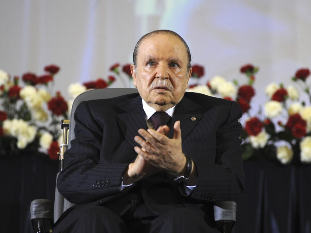 In this April 28, 2014 file photo, Algerian President Abdelaziz Bouteflika, sitting in a wheelchair, applauds after taking the oath as President in Algiers. One year after he was re-elected to a fourth term, the absence of Algeria's stroke-hit president from daily life is being felt more keenly than ever as this oil-rich North African nation is facing unprecedented economic and political challenges. (AP Photo/Sidali Djarboub, File)