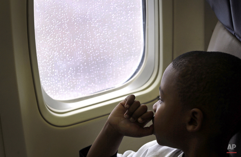 Xavier Perry, 5, looks out of an airplane window at Baltimore-Washington International Thurgood Marshall Airport, Saturday, Dec. 6, 2014, in Linthicum, Md., during Wings for Autism, an airport rehearsal for children with autism spectrum disorders, their families and aviation officials. Families took part in a typical airport experience, from check-in and security to boarding a plane, with the intention of alleviating some of the stress of air travel for children with autism. (AP Photo/Patrick Semansky)