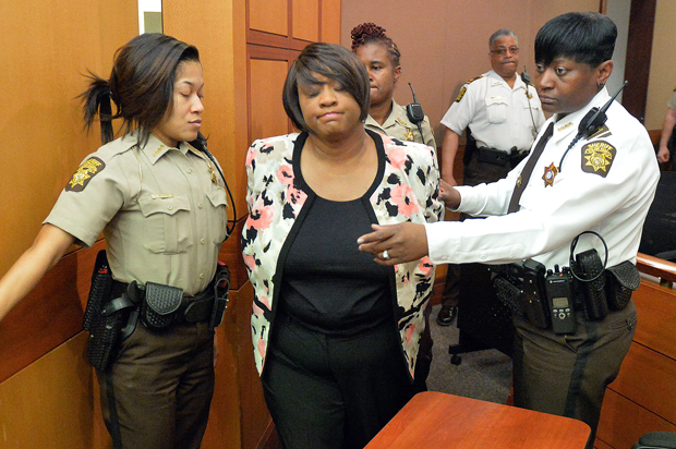 Former Atlanta Public Schools school research team director Tamara Cotman, center, is led to a holding cell after a jury found her guilty in the Atlanta Public Schools test-cheating trial, Wednesday, April 1, 2015, in Atlanta. Cotman and 10 other former Atlanta Public Schools educators accused of participating in a test cheating conspiracy that drew nationwide attention were convicted Wednesday of racketeering charges. (AP Photo/Atlanta Journal-Constitution, Kent D. Johnson, Pool)