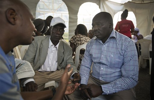 David Tomno Ngetich, right, whose niece Romana Chelagat Sambu, 21, died in the Garissa University College attacks, talks with other relatives who lost family members, as they sit under a tent in the courtyard of the Chiromo Funeral Parlour in Nairobi, Kenya Monday, April 6, 2015. Several mourners interviewed by The Associated Press spoke wistfully of those they lost, sometimes using the same words - humble, devout, studious and a role model - to describe youths who were trying hard to forge a career, leaving home and traveling many hours by bus to Garissa to take advantage of the education opportunities there. (AP Photo/Ben Curtis)