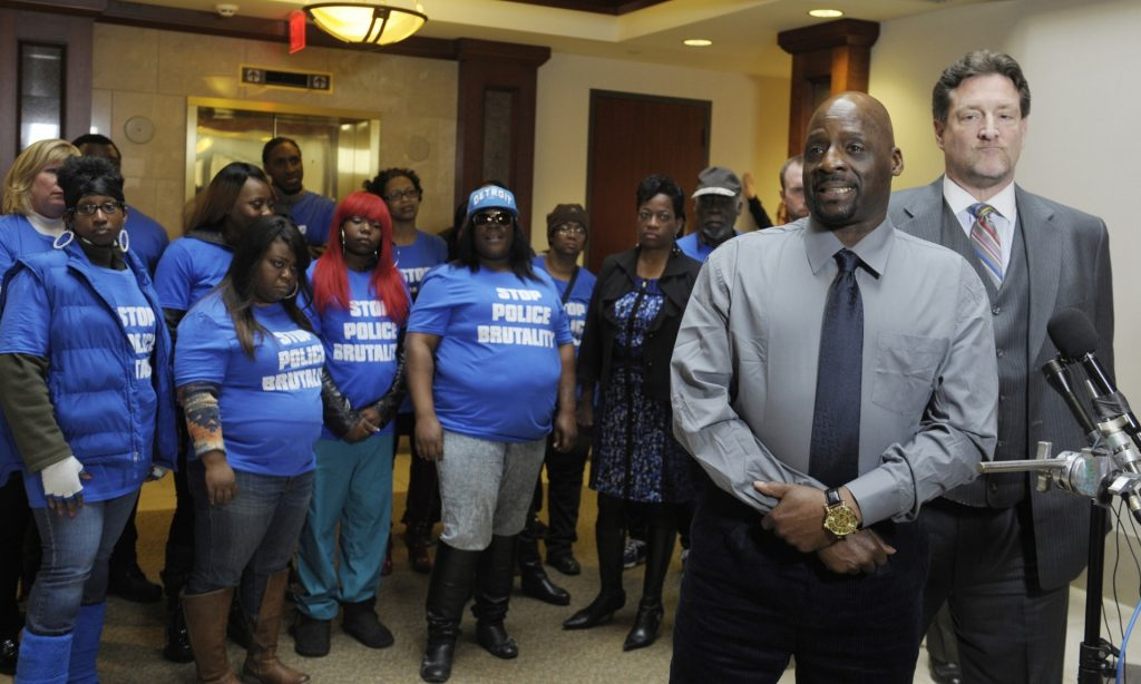 Protesters stand behind Floyd Dent as he speaks to the media. (Clarence Tabb Jr/AP Photo)