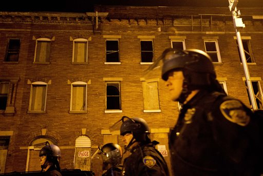 Police in riot gear walk past boarded up row homes after a 10 p.m. curfew went into effect Wednesday, April 29, 2015, in Baltimore. The curfew was imposed after unrest in Baltimore over the death of Freddie Gray while in police custody. (AP Photo/David Goldman)